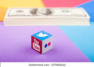 KAZAN, RUSSIA - April 15, 2019: Paper cube with Youtube, Twitter and Flickr logos and a stack of dollars in the background. Earnings in social networks