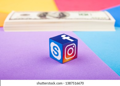 KAZAN, RUSSIA - April 15, 2019: Paper cube with Facebook, Instagram and Skype logos and a stack of dollars in the background. Earnings in social networks