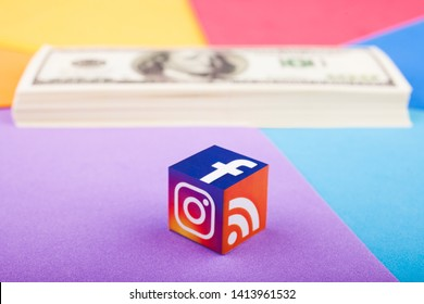KAZAN, RUSSIA - April 15, 2019: Paper cube with Facebook, Instagram and WiFi logos and a stack of dollars in the background. Earnings in social networks