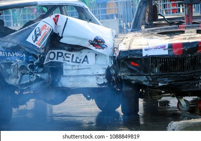 KAZAN, RUSSIA - APRIL 29, 2018: Extreme auto show - car revolt. Cars and drivers in  small arena compete in derby with  demolition. Fighting cars for survival after severe collisions and acciden
