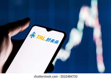 Kazan, Russia - August 10, 2021:  TAL Education Group is a Chinese company that offers after-school education for students. A smartphone with the TAL logo in a hand. Stock chart on the background.