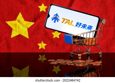 Kazan, Russia - August 10, 2021:  TAL Education Group is a Chinese company that offers after-school education for students. A smartphone with the TAL logo in food basket on the of the Chinese flag.