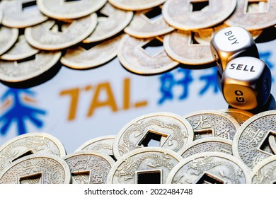 Kazan, Russia - August 10, 2021:  TAL Education Group is a Chinese company that offers after-school education for students. Dices with the words SELL BUY. TAL logo surrounded by feng shui coins.
