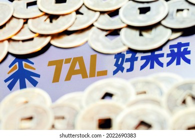Kazan, Russia - August 10, 2021:  TAL Education Group is a Chinese company that offers after-school education for students. TAL logo surrounded by blurred feng shui coins.