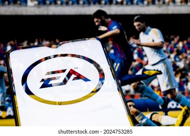 Kazan, Russia - August 14, 2021:  Electronic Arts Inc. is an American video game company. Electronic Arts logo on smartphone screen. A frame from the FIFA franchise game on the background.