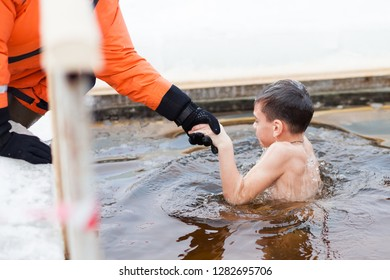KAZAN, RUSSIA, JANUARY 19, 2018: A child with the help of rescuers plunges into an ice hole at the Feast of Epiphany
