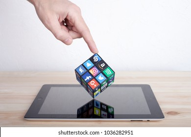 KAZAN, RUSSIA - January 27, 2018: Man's hand holds a cube with collection of popular social media logos on a tablet PC