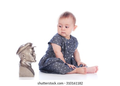 "KAZAN, RUSSIA - JULY 7, 2015: Baby girl sitting on floor in photo studio and looking on vintage Lenin's sculpture bust, concept ""don't know who is""."