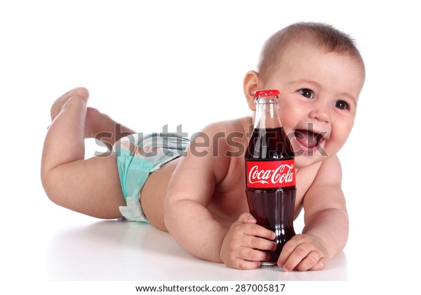 KAZAN, RUSSIA - JUNE 5, 2015: Happy baby with classic Coca-Cola bottle. Coca-Cola is a carbonated soft drink sold throughout the world.