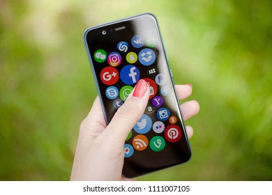 KAZAN, RUSSIA - JUNE 6, 2018: Woman pointing on social media icons on a smartphone