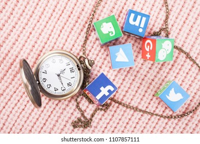 KAZAN, RUSSIA - March 06, 2018: paper cubes with popular social network logos and clocks with chain in a shape of heart on a knitted texture Facebook, Insta etc