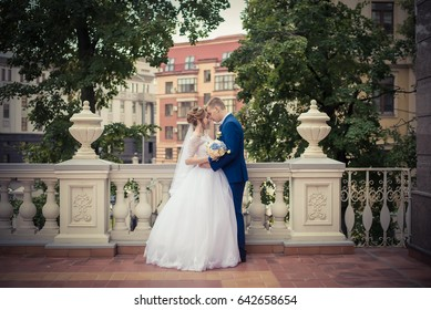Kazan, Russia - SEPTEMBER 2, 2016: Young beautiful wedding couple standing arm in arm on a background of white railing with vases