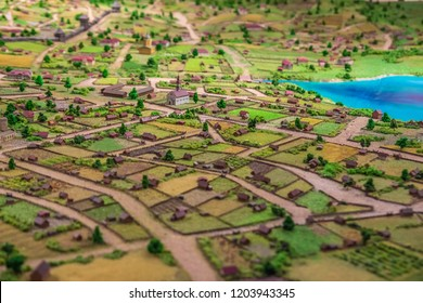 Kazan, Russia - September 3, 2017:  Exhibition City View. Miniature layout, model or maquette of landscape of countryside or village with small houses, roads and blue lake. Selective focus.