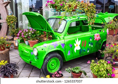 Kazan, Russia - September 9, 2018: Flowers composition with green retro car