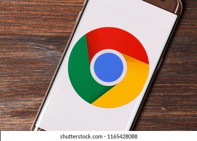 Kazan, Russian Federation - Aug 5, 2018: Man holding smartphone with Google chrome logo on the screen. Laminate wood background.