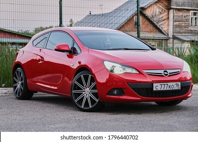 KAZAN, TATARSTAN, RUSSIA - 16 JUNE 2020: Front side view of Red colored Opel Astra coupe 2010 edition on the urban background. Supercharged cars. More car images download in my catalog.
