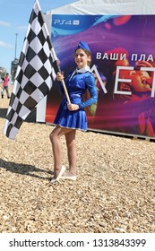 Kazan, Tatarstan, Russia - August 26: Red Bull Air Race, girl with a smile in a stewardess costume holding a checkered flag 26 August 2018