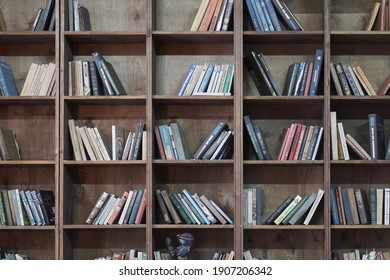 Kazan, Tatarstan, Russia - January 2021: Even rows of wooden shelves with different books in Russian language. Interior decoration. Concept of library and education. Bookstore. Selective focus.