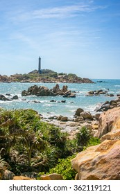 Ke ga lighthouse in Phan Thiet region, Vietnam. View from the shore, blue water and huge colorful stones on the beach (yellow sand), green plants in the front, vertical