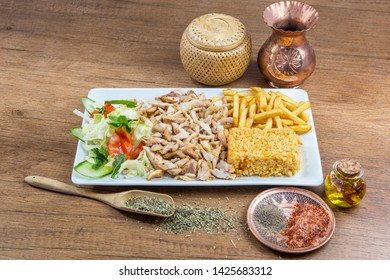 Kebab dish with french fries and salad on white plate, served with decoration in a wooden table