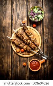 Kebab with fresh salad of cucumbers and onions. On wooden background.