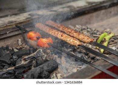 Kebab or kebap on metal skewer barbecue in the kebap restaurant. Traditional Turkish Adana Kebab