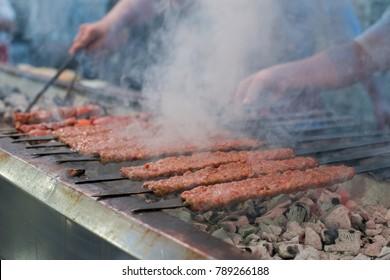 Kebab or kebap on metal skewer barbecue and embers in the kebab restaurant. Skewering bbq Kebab. Traditional Turkish Adana Kebab