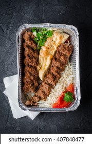 Kebab with rice and flatbread in box on dark background. Selective focus
