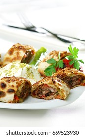 Kebab rolled in flat bread, on a white plate on white background