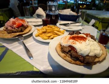 Kebab under Greek yoghurt on a pita - delicious food in a Greek tavern on a warm evening in Athens, Greece