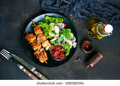 kebab and vegetable salad on plate., fried meat