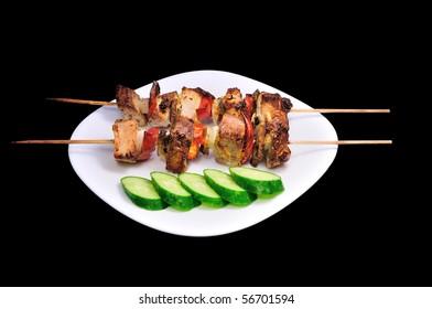 kebab with vegetables on black bacround