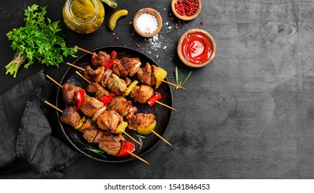 Kebabs - grilled meat skewers, shish kebab with vegetables on black wooden background.