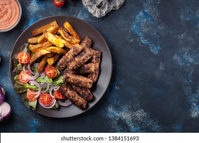 Kebapche or cevapcici, balkan minced meat kebab with french fries and salad