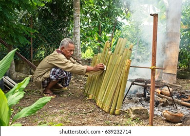 Kedah, Malaysia 8 July 2016: A man attending his lemang cooking for Hari Raya Aidil Fitri. Lemang is a Malaysian traditional delicacy where glutinous rice is cook in bamboo slow cook over wood fire.
