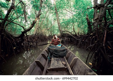KEDAH STATE , MALAYSIA , 20 AUGUST 2017 : The mangrove fisherman paddle the boat in the river to catch mangrove crab .