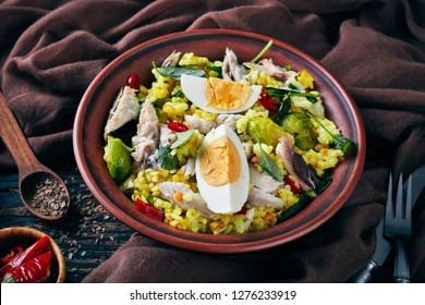 Kedgeree with flaked smoked fish, hard boiled eggs, rice, kale, brussel sprouts, spices and herbs in a bowl on an old wooden table with fennel seeds,  view from above, close-up