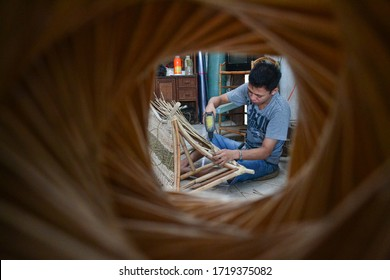 KEDIRI, INDONESIA - APRIL 27, 2016: A man is making crafts from rattan in a wood craft shop in Kediri, Indonesia.