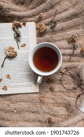 Kediri, Indonesia - January 2021: A cup of tea with sunglasses, dried flowers and a book of page from 'The Great Gatsby by F. Scott Fitzgerald' on  brown sweater