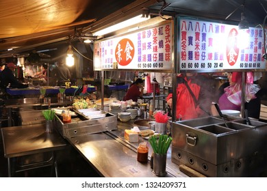 KEELUNG, TAIWAN - NOVEMBER 22, 2018: Vendors prepare food at famous Miaokou Night Market in Keelung, Taiwan. Night markets are essential part of Taiwanese food culture.