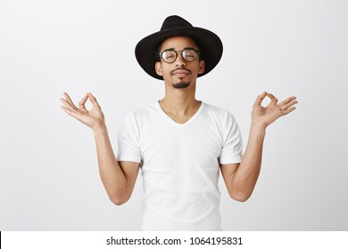 Keep calm and carry on. Studio portrait of relaxed handsome african-american fashion designer in stylish glasses and hat, raising hands with zen gesture, meditating or doing yoga, calming down