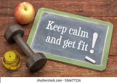 Keep calm and get fit -  slate blackboard sign against weathered red painted barn wood with a dumbbell, apple and tape measure