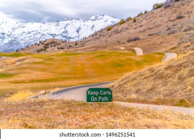 Keep Carts On Path sign beside a narrow pathway that winds through a grassy hill