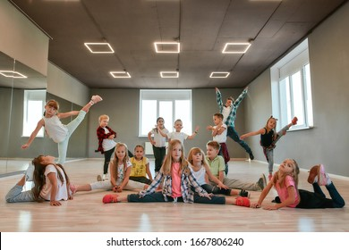 Keep dancing. Group of happy little boys and girls in fashionable clothes posing together in the dance studio. Dance team. Hip hop