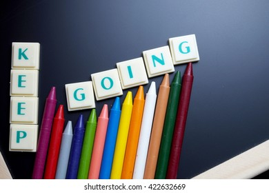 Keep going concept. The words spelled by letters with crayon drawing on blackboard with wooden border. Space for texts. Dark tone.