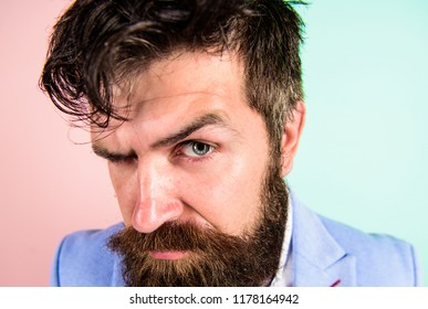 Keep hair tidy and care about hairstyle. Man bearded hipster on strict face pink blue background. Barber tips grooming beard. Hipster guy with messy tousled hair and long beard needs barber service.