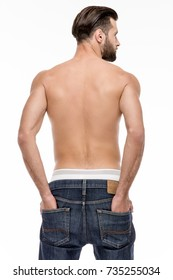 Keep it in his pockets. Rear view of young shirtless man in jeans looking away while standing against white background.