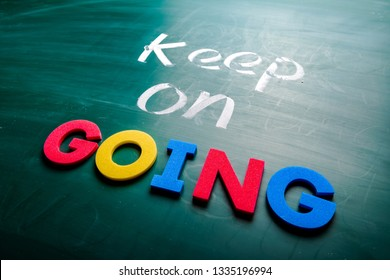 Keep on going concept. Colorful and handwriting words on blackboard.