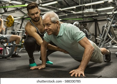 Keep pushing! Full length shot of a fitness trainer physiotherapist helping his senior client doing pushups workout exercising training retired elderly health strength motivation dedication concept