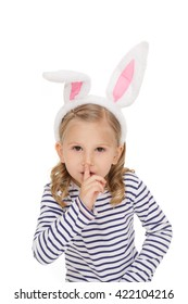 Keep quiet! Studio shot of a little pretty gir wearing bunny ears shushing to the camera seriously isolated on white
